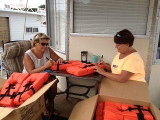 Debbie Felgenhauer and Diana Baldwin preparing the child life jackets for use.